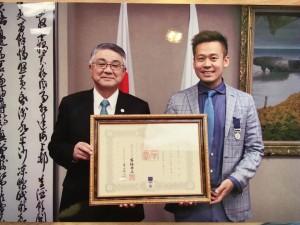 紺綬褒章を受賞し天草市長と写真を撮る竹井佑介